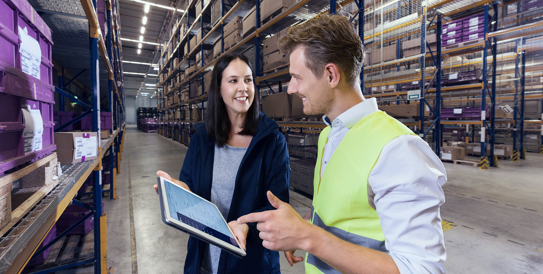 Digital logistics woman and man with a tablet working in the warehouse