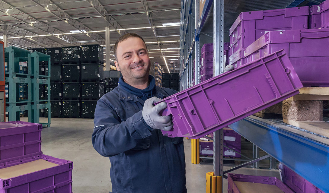 Warehouse worker sorting purple boxes