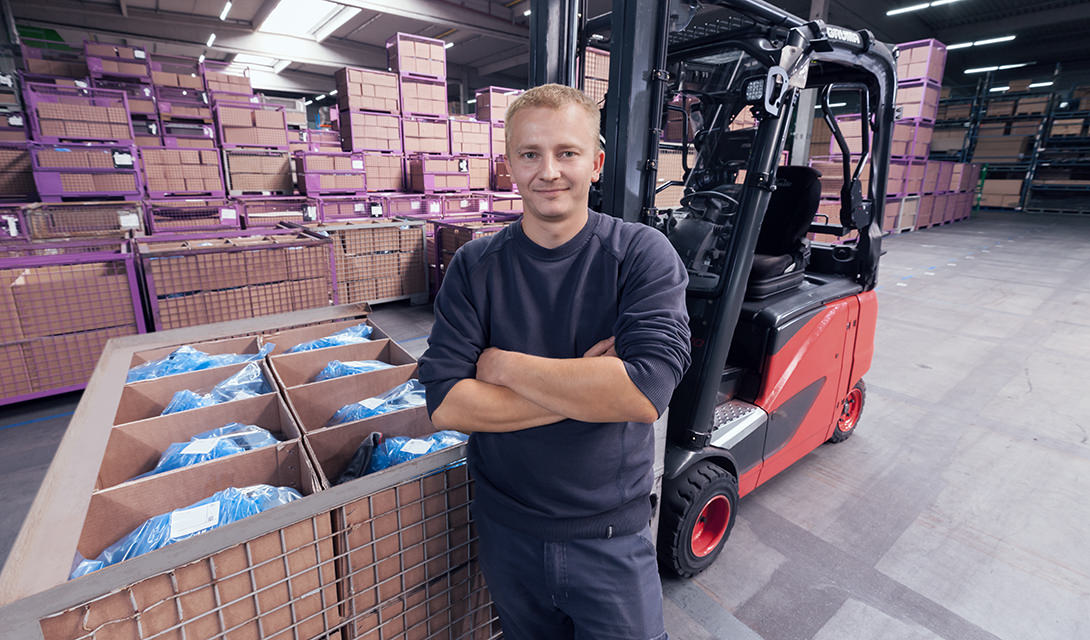 Warehouse worker in front of a forklift and boxes